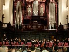 L'orchestre se prépare : les musiciens répètent chacun dans leur coin des bouts de partitions. Cela fait une drôle de mélasse cacophonique.