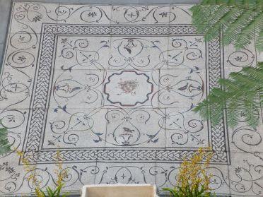 Focus sur la mosaïque au centre de la cour avec une tête de Méduse.