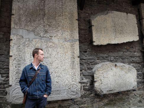 L'archéologue devant les pierres tombales.