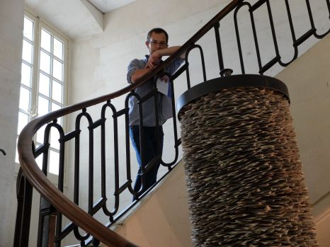 Posant dans les escaliers à côté d'une oeuvre d'art...