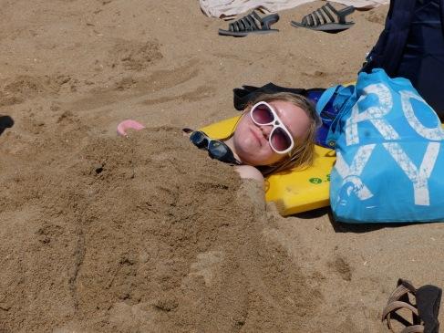 Leisan profite de quelques minutes ensevelie dans le sable avant de repartir barboter avec sa planche.