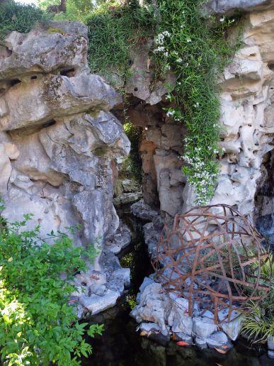 Le ruisseau, la végétation tombante et une sculpture d'art contemporain.