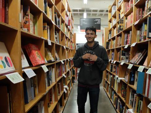 Isaiah entre deux rayons de livres parmi tant d'autres.