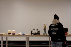 Llew (de dos) en face d'une des tables sur lesquelles sont exposées les objets d'art.