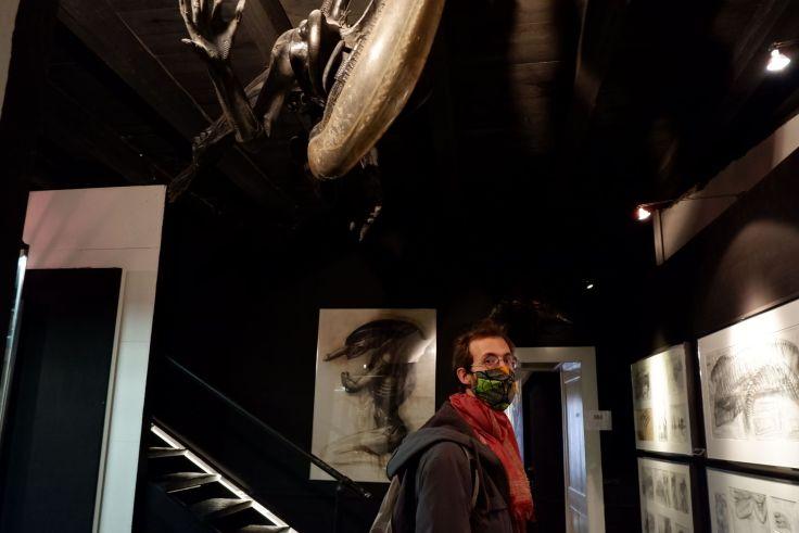 Ryan dans le musée H.R. Giger avec un alien au-dessus de lui