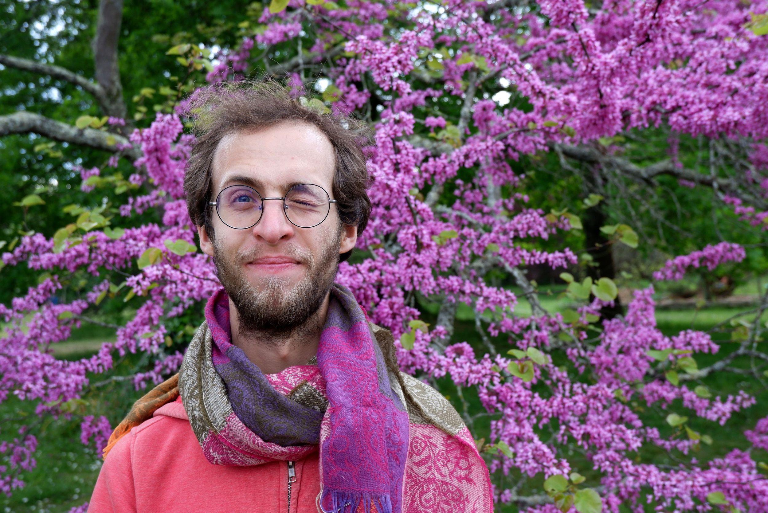 Ryan posant devant des fleurs violettes