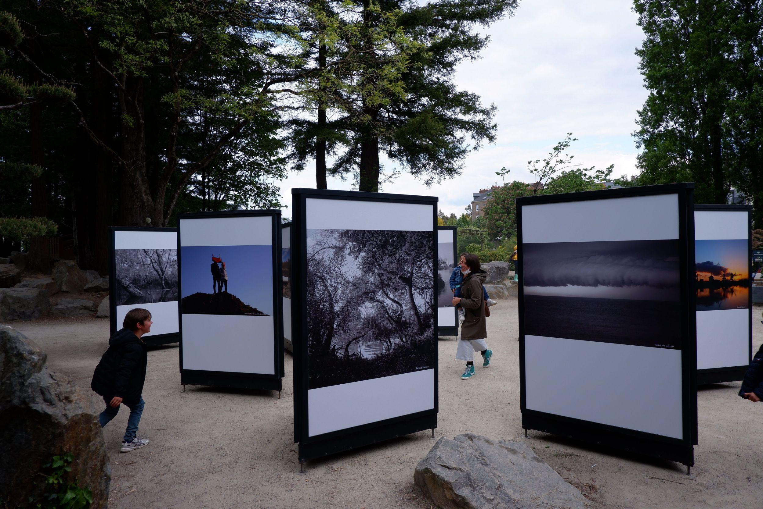 Des panneaux d'exposition sur l'île de Versailles et des gens qui jouent à chat entre les panneaux.