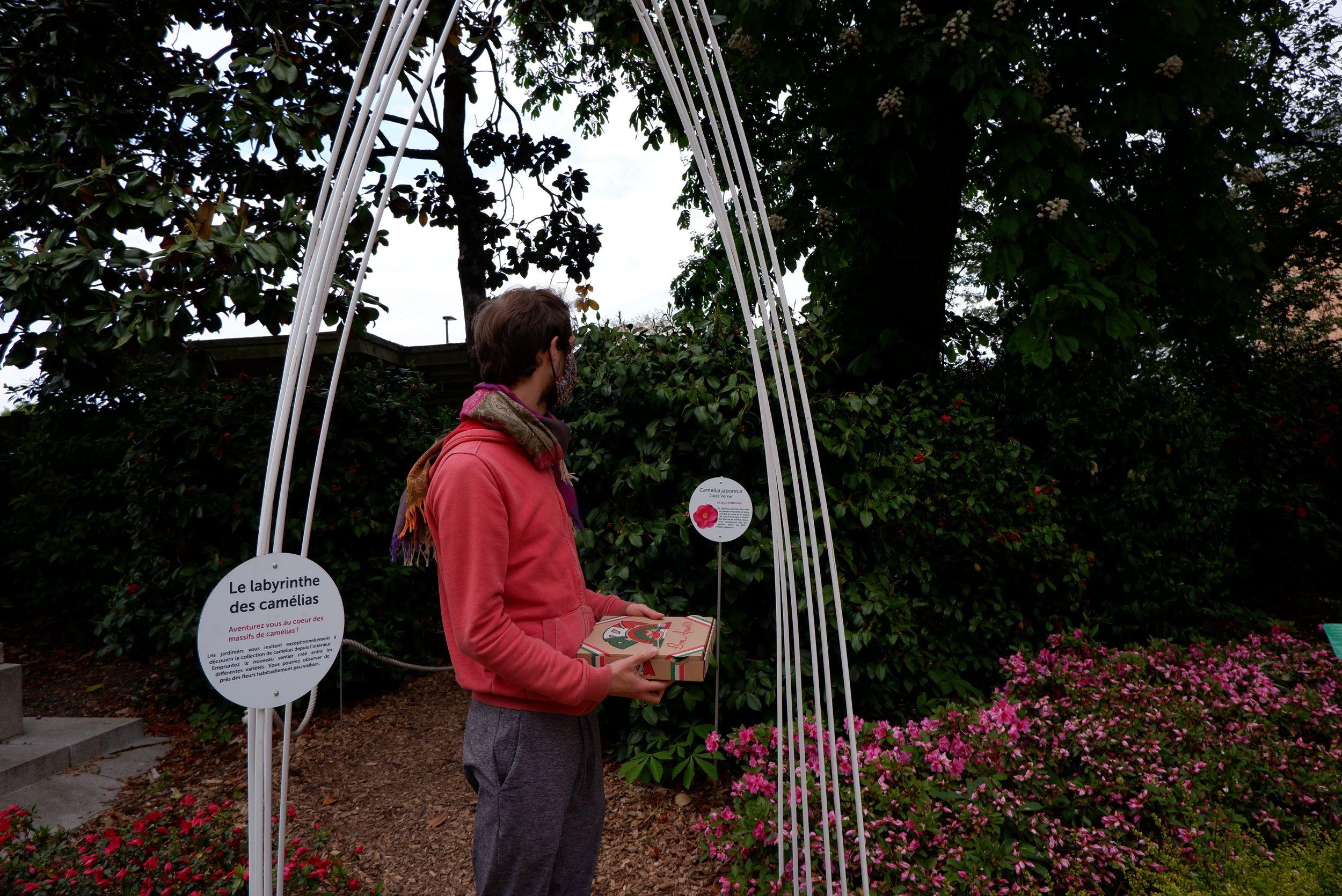 Ryan portant une pizza en face du labyrinthe des camélias dans le jardin des plantes