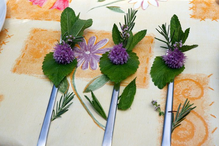 Trois fourchettes décorées de fleurs de ciboulette, menthe et romarin.