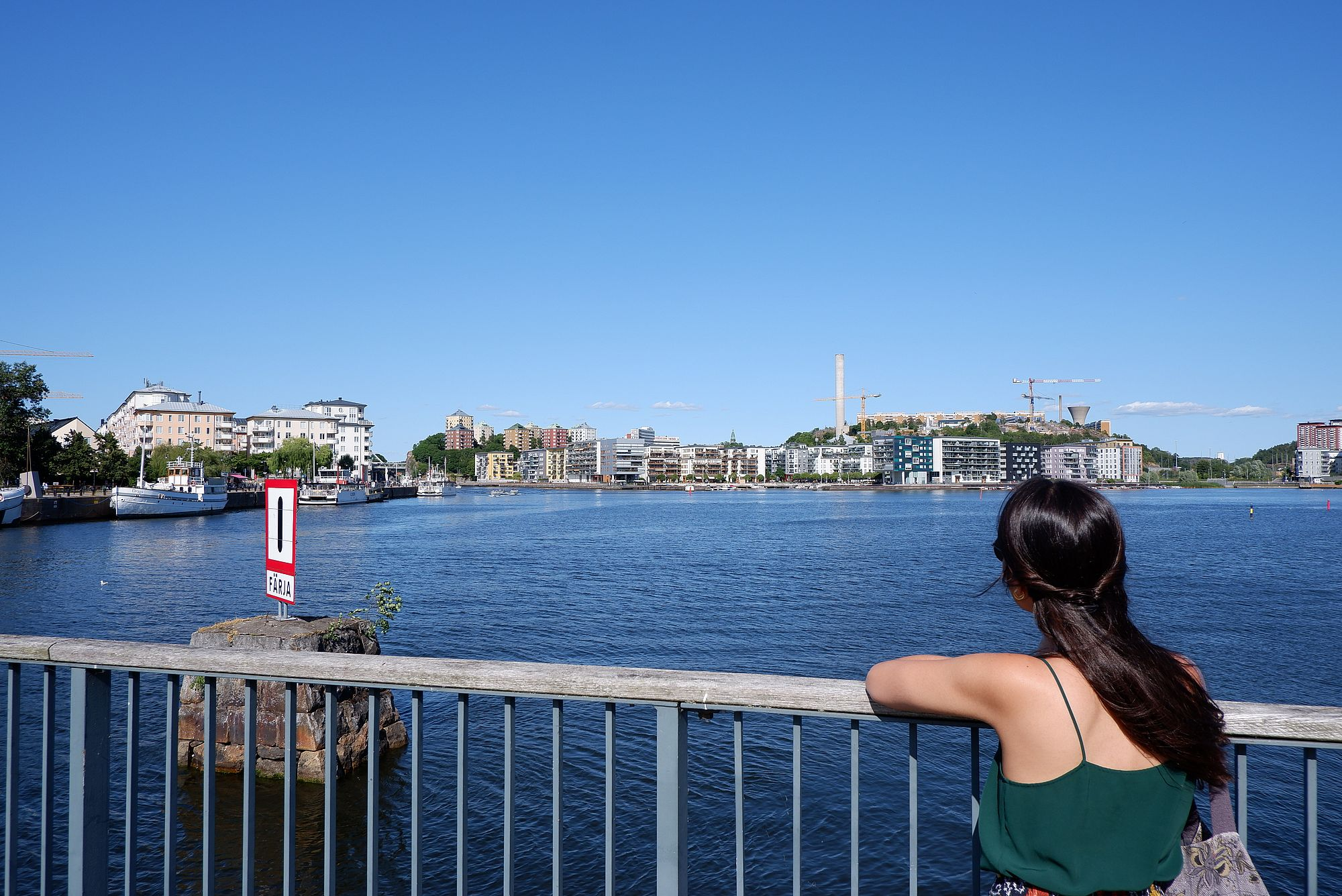 Marina appuyée contre une rambarde au bord de l'eau à Stockholm.