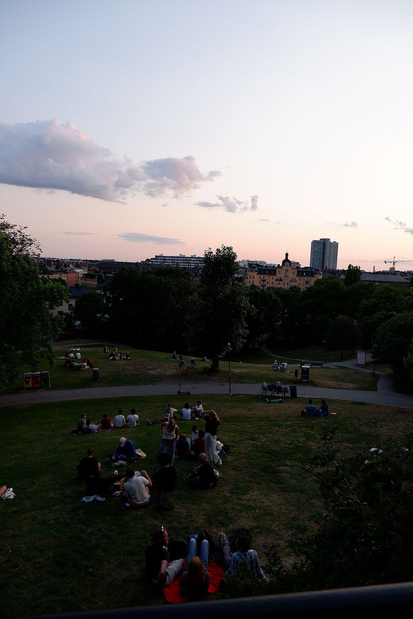 des groupes de personnes assises ou allongées dans l'herbe, le soir à Stockholm.