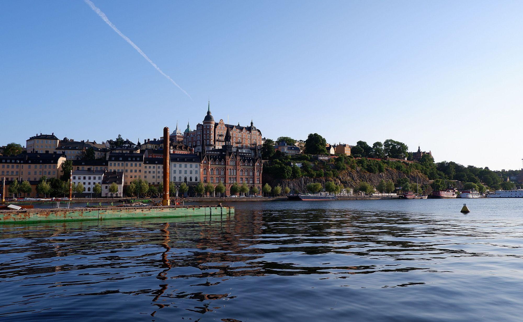 Un paysage représentant Stockholm avec une grande étendue d'eau au premier plan et des bâtiments pittoresques en arrière-plan, quasiment perchés sur la falaise.