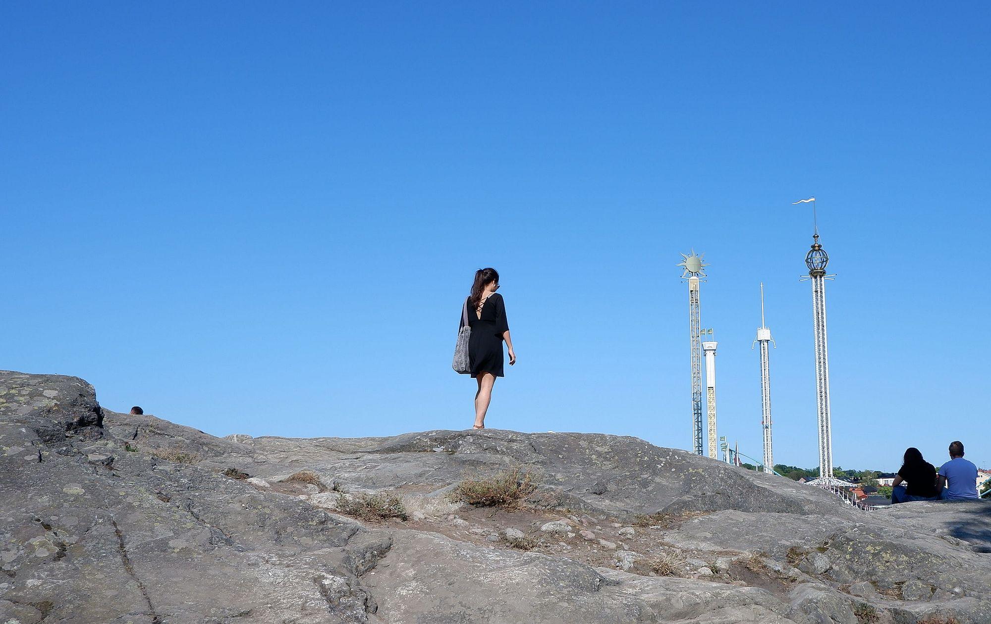Marina se promenant sur un chemin rocheux en face d'un parc d'attraction.