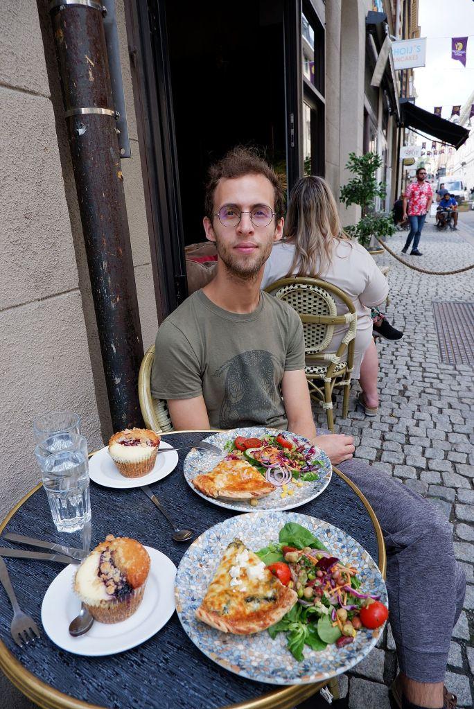 Ryan attablé au Muffin Bakery, devant nos assiettes de tartes salées et de muffins sucrés.