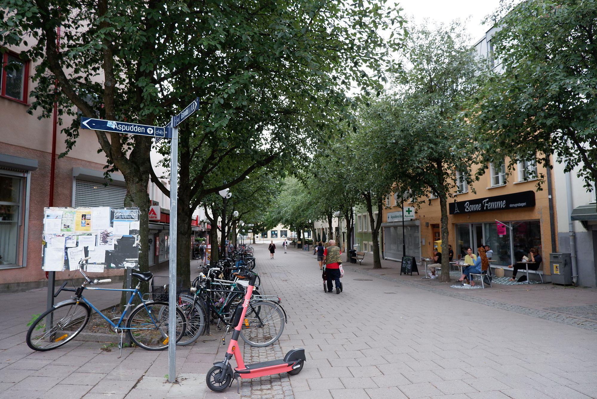La sortie du métro à Aspudden : ruelle pavée avec des vélos et des petits commerces comme une boulangerie qui porte le nom de Bonne Femme