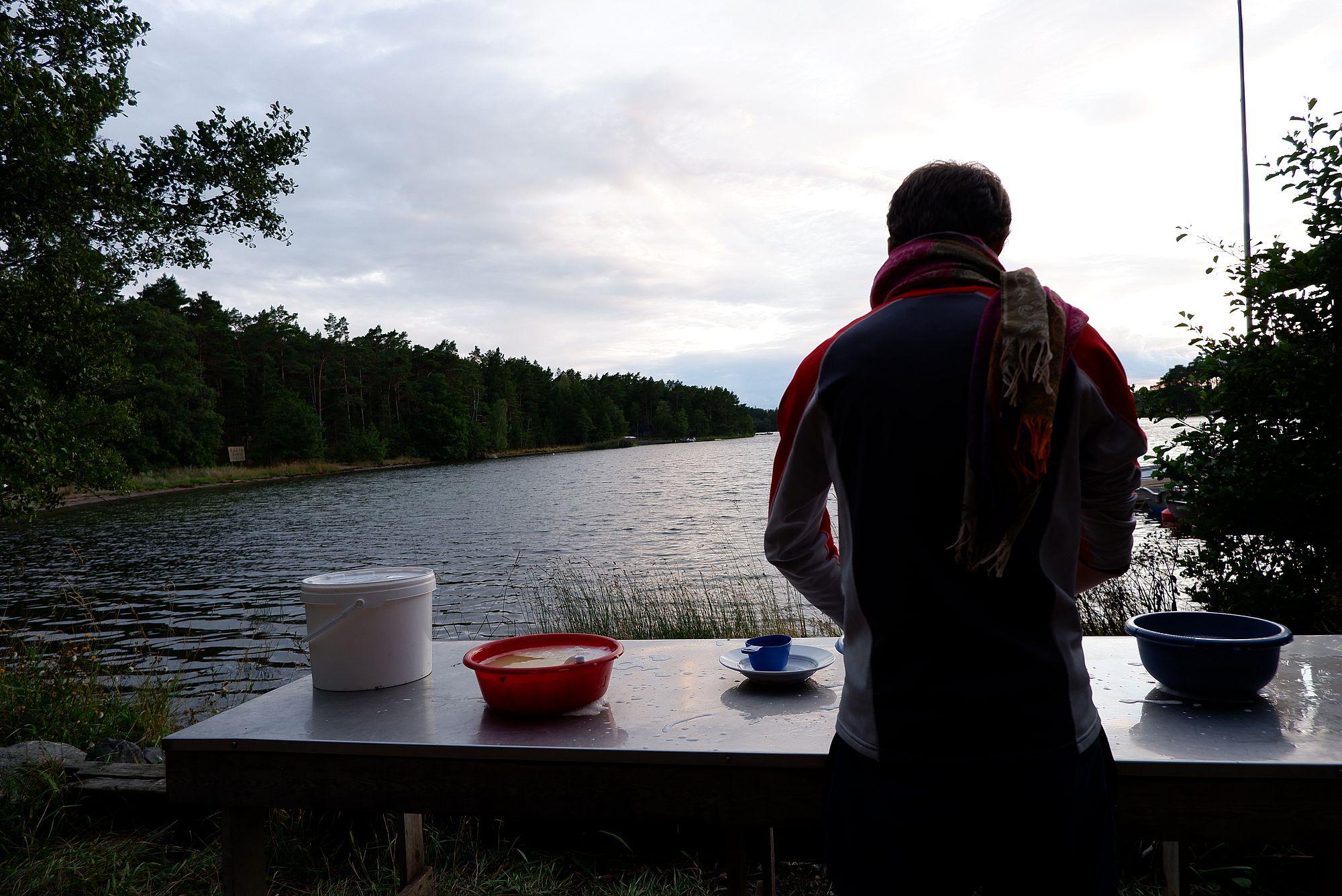 Ryan fait la vaisselle dehors face à l'eau.
