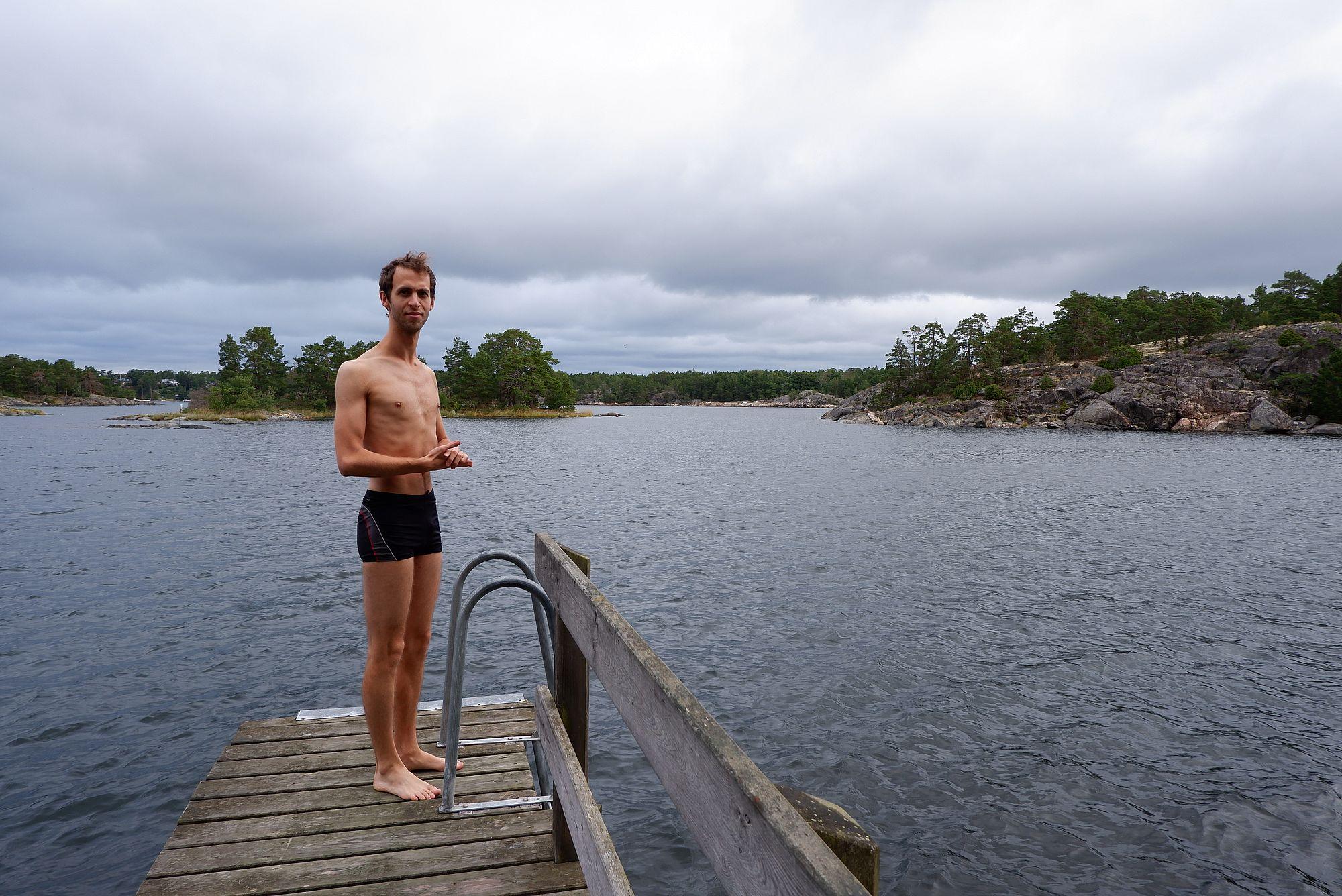 Ryan en maillot de bain sur un ponton au bord de l'eau