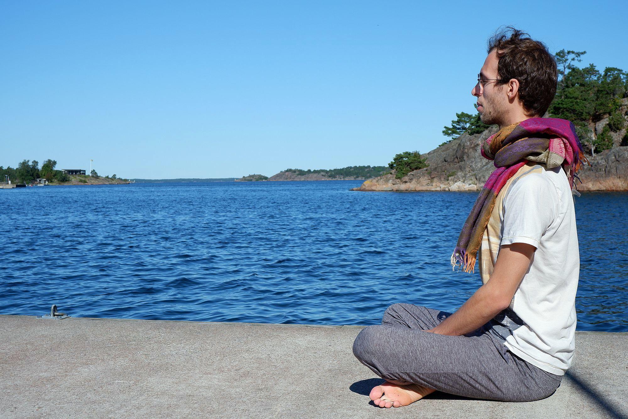 Ryan médite sur un ponton au bord de l'eau, sous le soleil