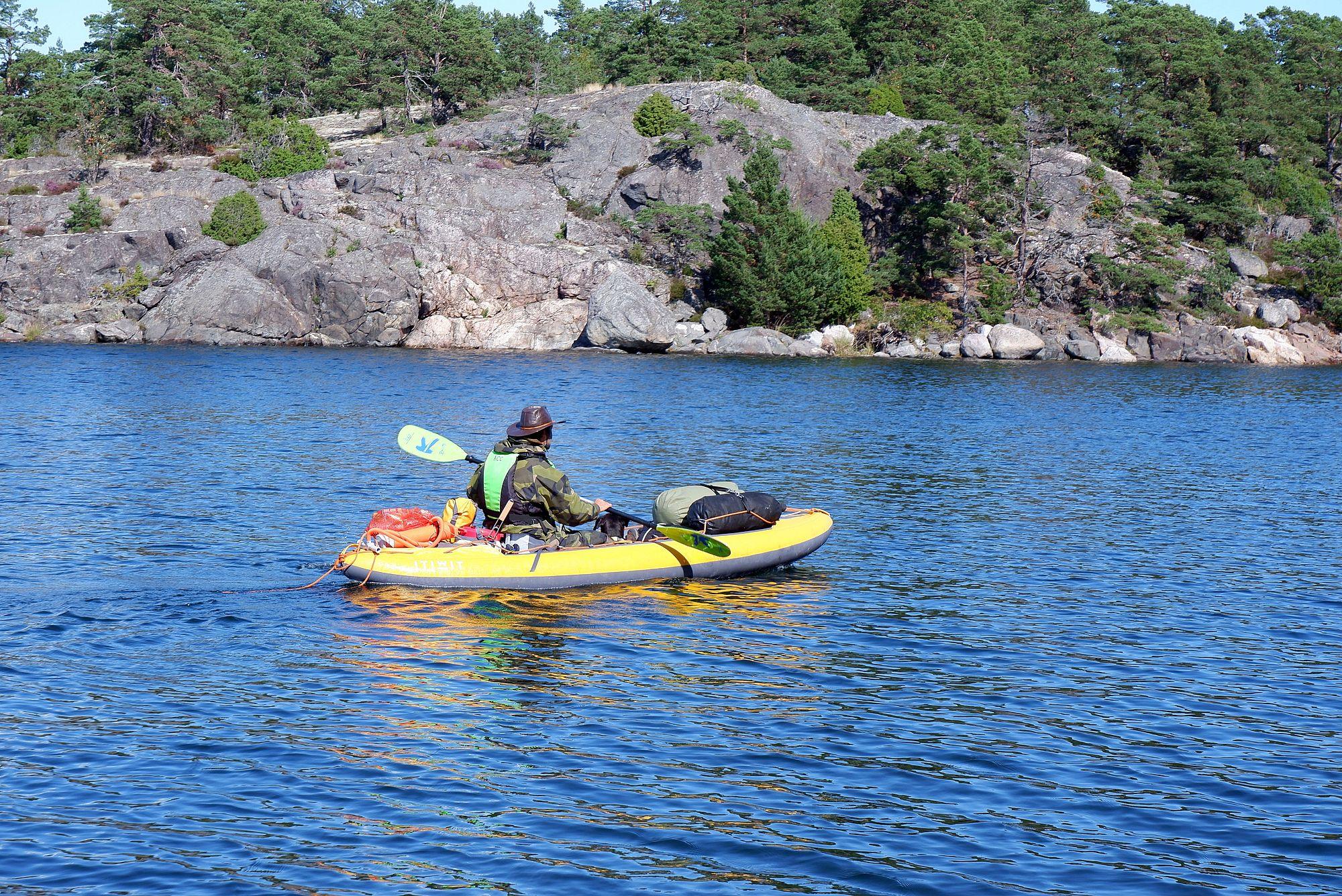 Un homme sur un kayak gonflable jaune avec plein de sacs et un chien allongé
